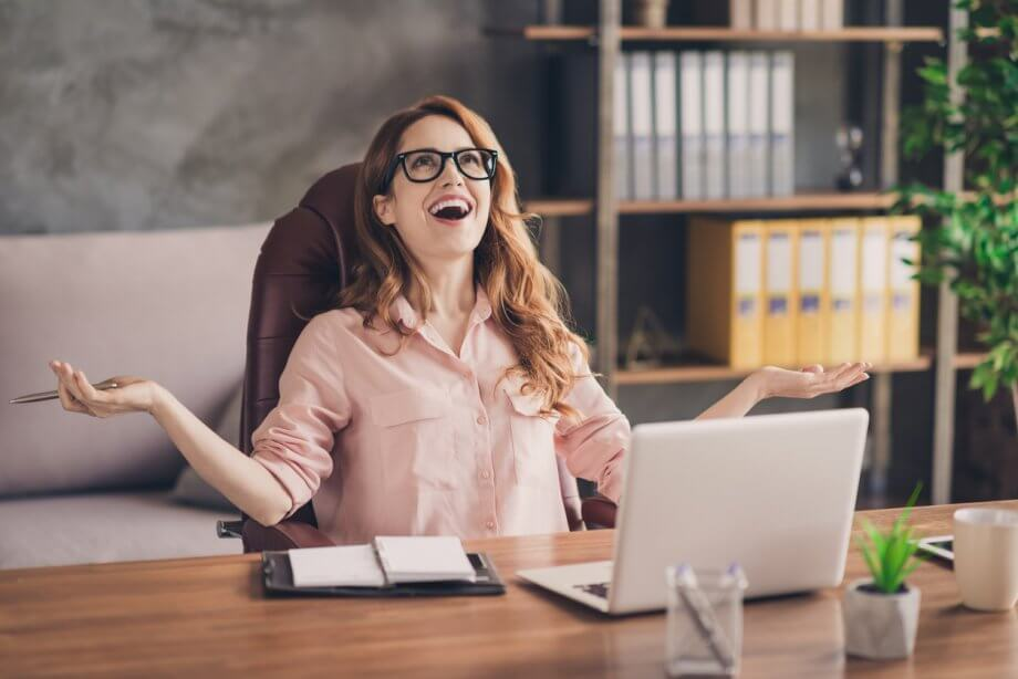 Photograph of a woman with glasses & wavy red hair sitting in an office chair seemingly happily surprised